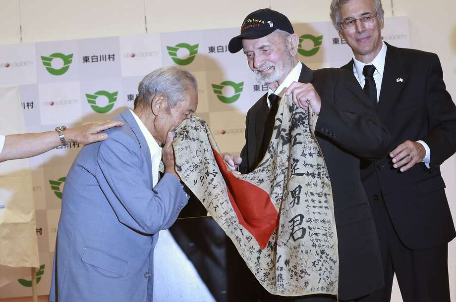 Tatsuya Yasue smells the flag of his late brother, Sadao Yasue, returned to him by Marvin Strombo. Photo: Eugene Hoshiko, Associated Press
