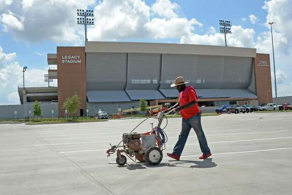 A worker paints stripes for parking spaces at Legacy Stadium in Katy, TX on July 13, 2017.