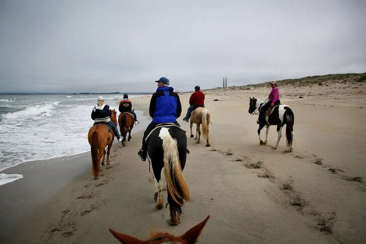 Monterey Bay Equestrian Center trail guide Lisa Soares-Earley (far right) leads a group out horseback riding along Salinas River State Beach in Castroville, Calif., on Friday, May 23, 2014.