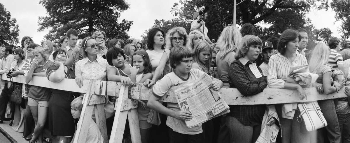 A crowd gathers outside the gates of Graceland.