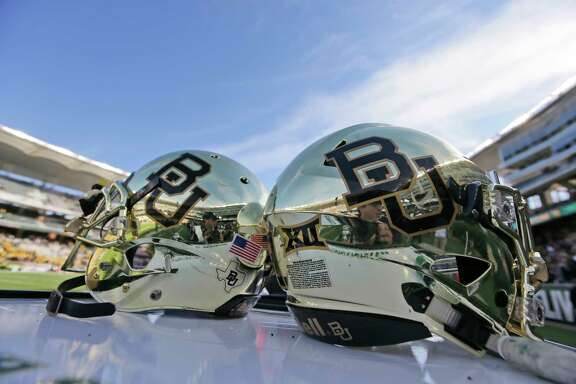 "FILE - In this Dec. 5, 2015, file photo, Baylor helmets on shown the field after an NCAA college football game in Waco, Texas. The NCAA is conducting an ""ongoing, pending investigation"" into Baylor University in the wake of a sexual assault scandal that led to the firing of football coach Art Briles and the departure of the school president, the school's lawyers confirmed in a federal court filing. (AP Photo/LM Otero, File)"