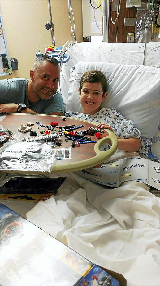 Officer Bruce Giovanelli and the boy he saved. Photo: Contributed Photo / Christine Oifer