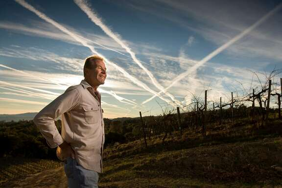 WINEMAKER07_140_cl.JPG Photo for story on this year's Winemaker of the Year and the five Winemakers to Watch. This is Josh Jensen of Calera Wine Company in Hollister. Josh Jensen is the Winemaker of the Year. Photo of Josh Jensen looking at the contrails of jet airliners criss crossing above his vineyard. His vineyard is along the pathway for jet airliners. on 11/15/07 in Hollister.  photo by Craig Lee / The Chronicle Ran on: 12-07-2007 Josh Jensen stands amid Calera's vines, which are rooted in limestone soil on Mount Harlan. Contrails of jets, whose flight paths crisscross above the vineyard, linger in the sky.