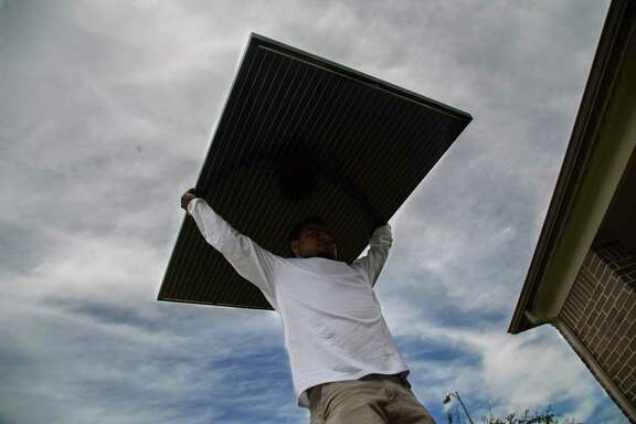 A worker prepares to install solar panels on a house in Katy.