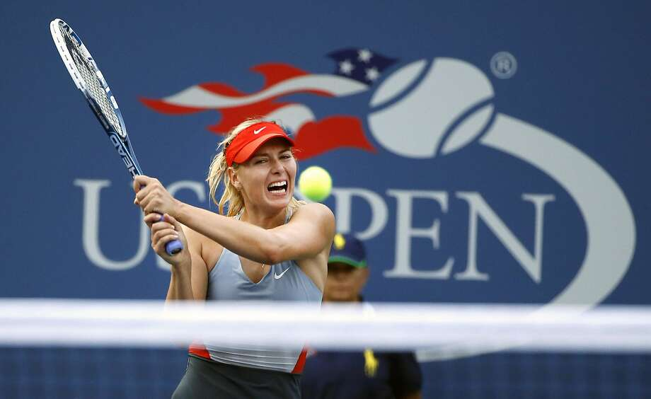 FILE - In this Aug. 27, 2014, file photo, Maria Sharapova, of Russia, returns a shot to Alexandra Dulgheru, of Romania, during the second round of the U.S. Open tennis tournament, in New York. Sharapova has been granted a wild-card invitation for the U.S. Open's main draw. Sharapova is among eight women who were given entry into the 128-player field by the U.S. Tennis Association on Tuesday, Aug. 15, 2017, and by far the most noteworthy. (AP Photo/Jason DeCrow, File) Photo: Jason DeCrow, Associated Press