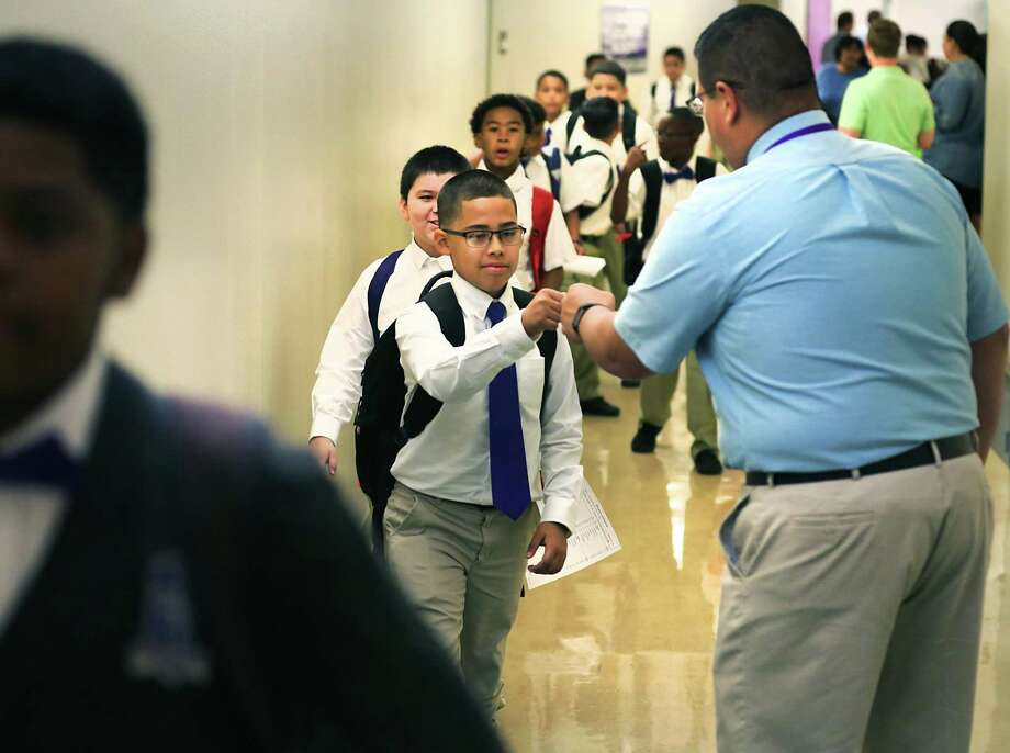 """Pete Rodriguez, right, Technology Applications teacher at Young Men's Leadership Academy greets students with a fist bump on their way to attend an assembly with special guest speakers Mayor Ron Nirenberg, City Councilman William H. (""""Cruz"""") Shaw III and San Antonio Fire Chief Charles Hood during the first day of school on Monday, Aug. 14, 2017. Photo: Bob Owen, Staff / San Antonio Express-News / ©2017 San Antonio Express-News"""