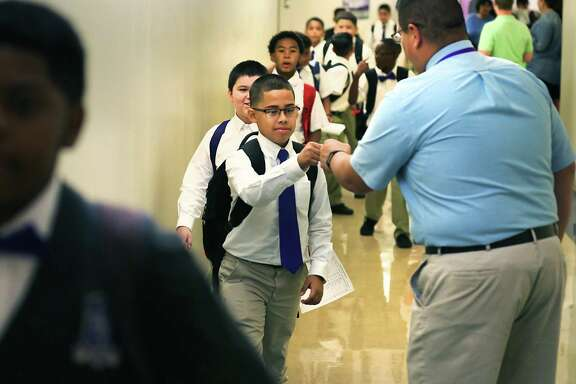 """Pete Rodriguez, a technology applications teacher at Young Men's Leadership Academy, greets students with fist bumps on their way to an assembly with special guest speakers Hood, Mayor Ron Nirenberg and City Councilman William """"Cruz"""" Shaw."""