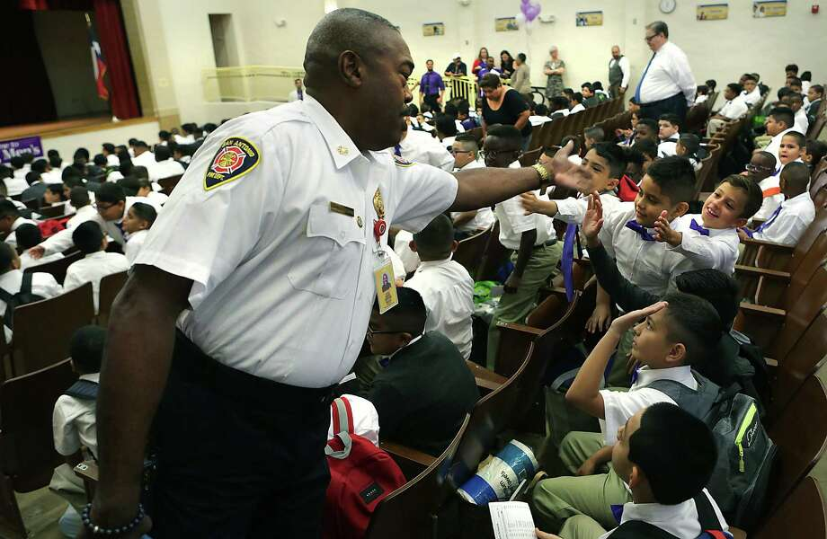 San Antonio Fire Chief Charles Hood greets students at Young Men's Leadership Academy as they attend an assembly with special guest speakers during the first day of school last August. Under financial pressure from dropping district enrollment, SAISD budget-writers don't want to change innovative school models like this one. Photo: Bob Owen /San Antonio Express-News / ©2017 San Antonio Express-News