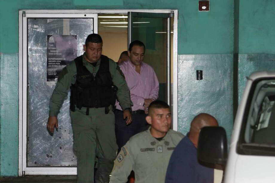 Roberto Borge, former governor of Mexico's state of Quintana Roo, top center, is escorted in  handcuffs by police after his extradition hearing in Panama City, Wednesday, Aug. 2, 2017. Borge will remain jailed in Panama until he is extradited to Mexico where he is wanted on corruption charges. (AP Photo/Arnulfo Franco) Photo: Arnulfo Franco, Associated Press / Copyright 2017 The Associated Press. All rights reserved.