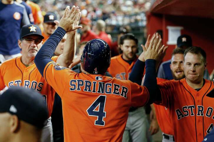 Houston Astros' George Springer (4) celebrates his run scored against the Arizona Diamondbacks with hitting coach Dave Hudgens, left, Max Stassi, second from right, and Brad Peacock, right, during the second inning of a baseball game Tuesday, Aug. 15, 2017, in Phoenix. (AP Photo/Ross D. Franklin)