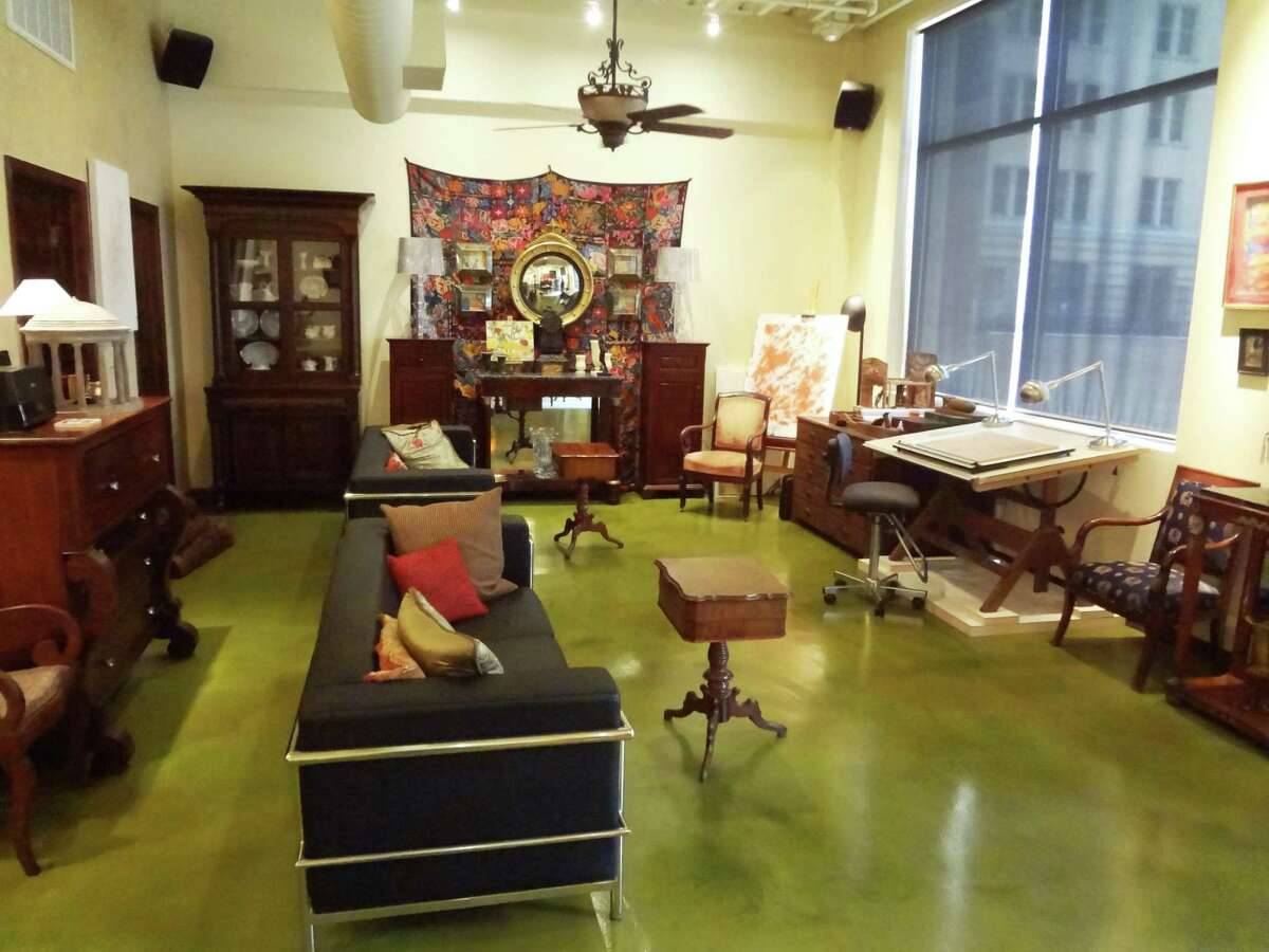 The living room features concrete floors painted a spring green, French antiques and modernist furniture.