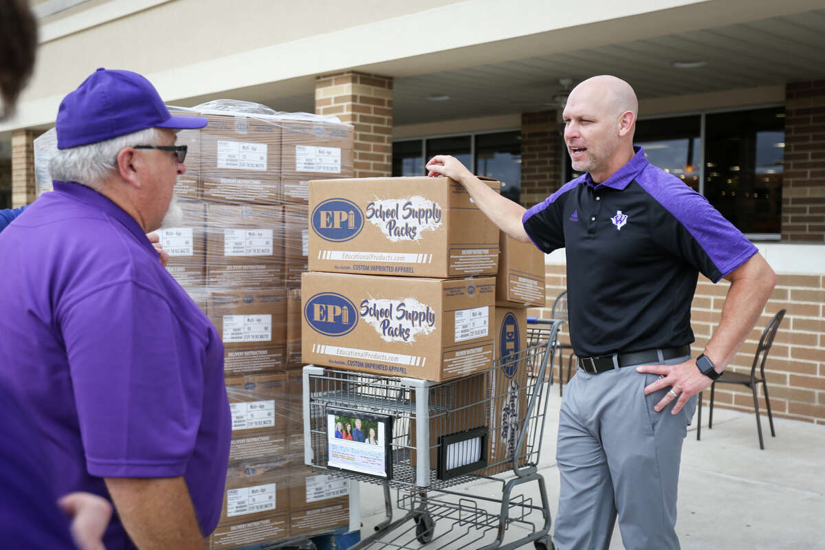 Willis ISD Superintendent Tim Harkrider, right, chats with Kroger Store Manager Mike Medved while standing next to almost $6,000 of donated school supplies on Friday outside the Kroger Marketplace in Willis.