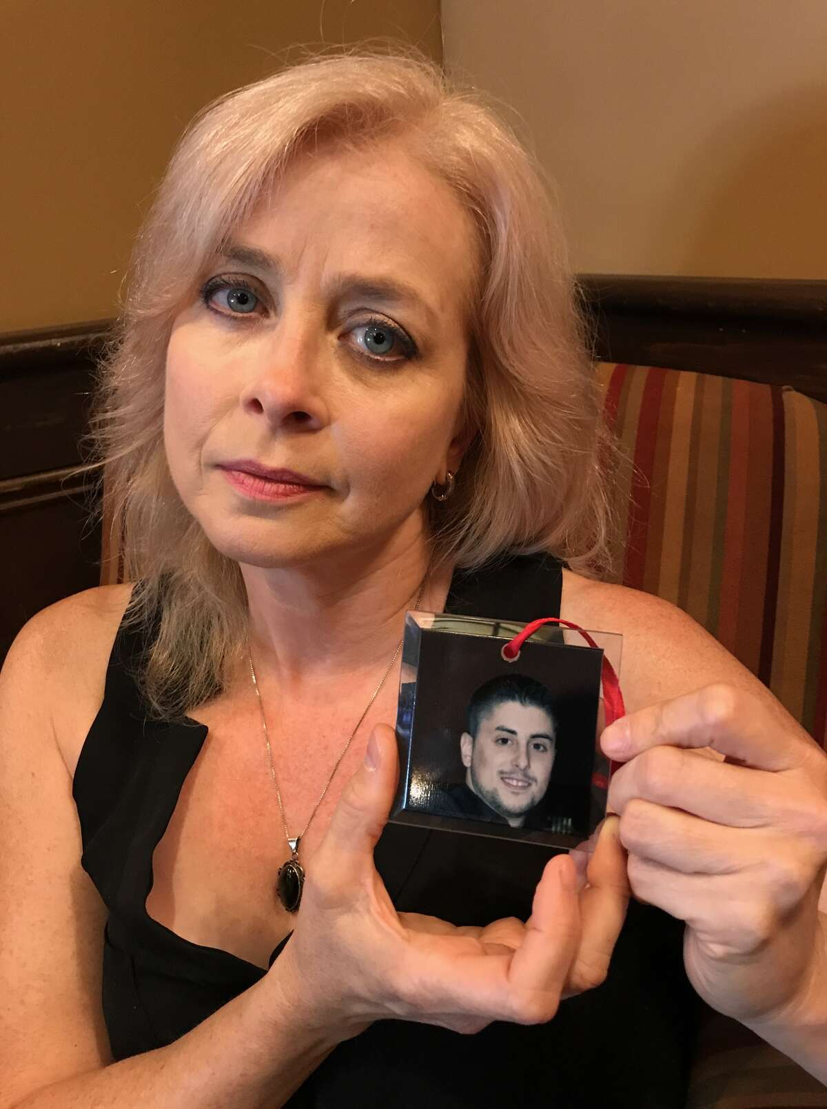 Karen Urban holds a Christmas tree ornament with a picture of her son, CJ (Paul Grondahl / Times Union)