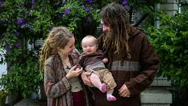 Parents Marielle Lowes, 24, and Paul Wassell (right) play with their son Donovan Wassell (center), 8-months while standing for a portrait near a friends house in San Francisco, Calif., on Wednesday, Aug. 9, 2017. Marielle Lowes and Paul Wassell had their RV towed July 27th and have been homeless ever since.