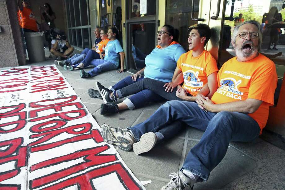 The front doors are blocked by a sitdown protest as millenials demonstrate their support for DACA programs in Austin. Photo: Tom Reel /San Antonio Express-News / 2017 SAN ANTONIO EXPRESS-NEWS