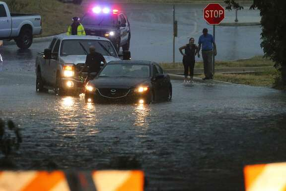 A car is removed from rain-swollen Salado Creek near Wurzbach Parkway and U.S.  281 North after heavy rain swept through the San Antonio area earlier this month. The $2.7 billion fiscal year 2018 budget, which goes into effect Oct. 1, increases spending on street maintenance by $35 million to $99 million.