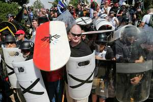 White nationalist demonstrators use shields Saturday as they guard the entrance to Lee Park in Charlottesville, Va.