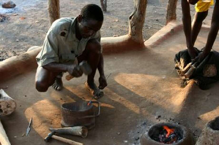Julius, the patriarch of Kambako Living Museum of Bushcraft, near the Malilangwe Wildlife Reserve, in Zimbabwe, teaches the fine art of forging spearheads from iron on Sept. 24. The museum is all about teaching others about African ancestral life.