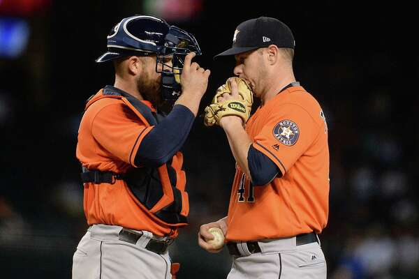 The Astros' battery of catcher Max Stassi, left, and Brad Peacock consult in the fourth inning, two innings after both had run-scoring doubles.