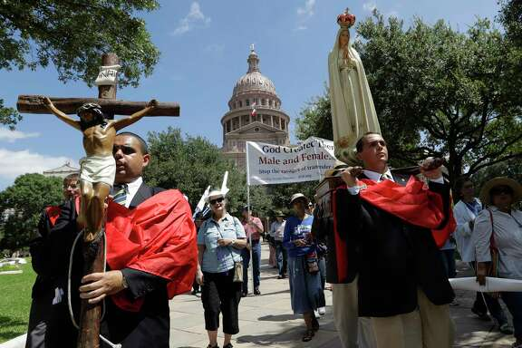 Cesar Franco, left, and Zecharia Long, right, lead members of Tradition, Family, Property, a group opposing the Texas 'bathroom bill', in procession following a prayer rally on the steps of the Texas Capitol, Tuesday, Aug. 15, 2017, in Austin. The bill is expected to fail despite strong support of Republican Gov. Greg Abbott, Lt. Gov. Dan Patrick and strong social conservatives who normally dominate state politics. (AP Photo/Eric Gay)