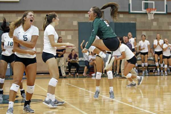 Reagan celebrates after winning the match, including Camryn Ennis,5, and Lydia Niebla,R. High school volleyball match between Reagan and Brandeis on Tuesday, August 15, 2017
