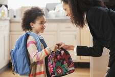 Mother handing daughter school lunch