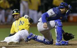 Oakland Athletics' Matt Joyce, left, slides to score past Kansas City Royals catcher Drew Butera in the eighth inning of a baseball game Tuesday, Aug. 15, 2017, in Oakland, Calif. Joyce scored on a single by Oakland's Marcus Semien. Athletics won, 10-8. (AP Photo/Ben Margot)
