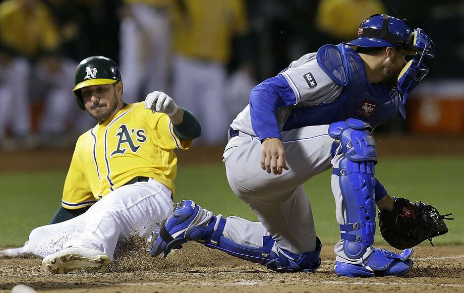 Oakland Athletics' Matt Joyce, left, slides to score past Kansas City Royals catcher Drew Butera in the eighth inning of a baseball game Tuesday, Aug. 15, 2017, in Oakland, Calif. Joyce scored on a single by Oakland's Marcus Semien. Athletics won, 10-8.  Photo: Ben Margot, Associated Press