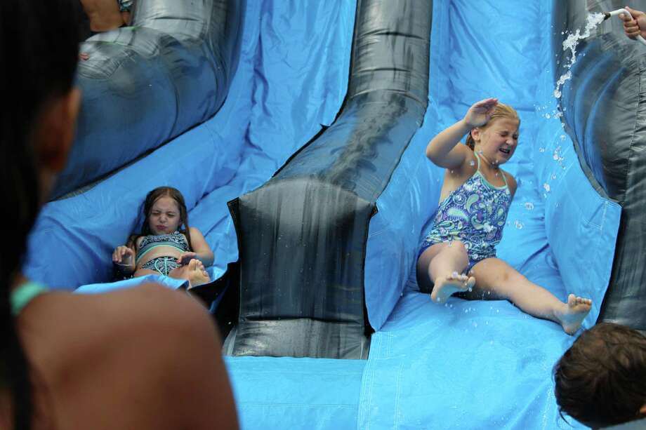 Lily Zane and Caitlin Cronin go down the water slide at Camp Looper on Tuesday, Aug. 15, 2017. Photo: Stephanie Kim / Hearst Connecticut Media