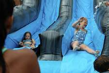Lily Zane and Caitlin Cronin go down the water slide at Camp Looper on Tuesday, Aug. 15, 2017.
