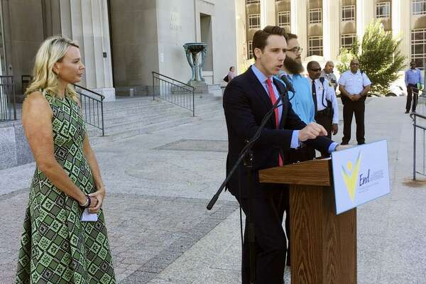 Missouri Attorney General Josh Hawley speaks at a news conference in June, in St. Louis where announced he is suing three large pharmaceutical companies, saying their deceptive marketing practices contributed to an opioid abuse crisis in the state. Looking on at left is Jammie Fabick, whose 17-year-old daughter died of an opioid overdose in 2014.