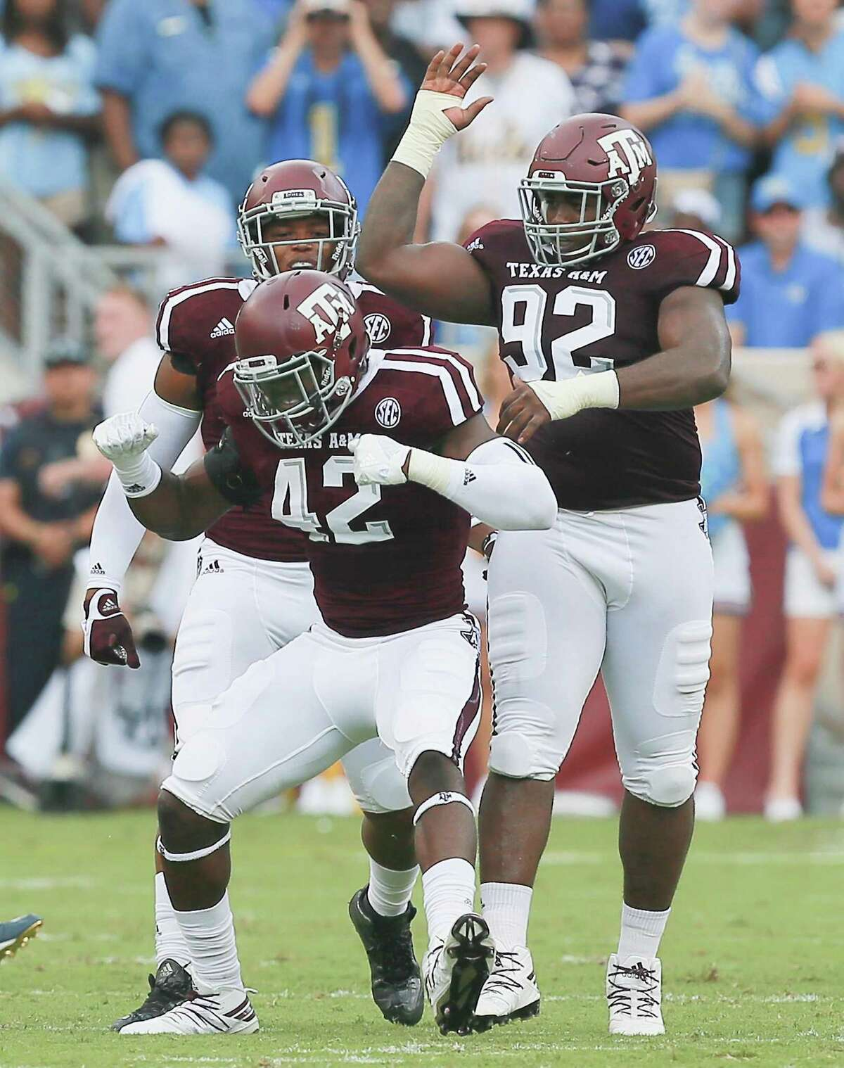 Otaro Alaka (42) of the Texas A&M Aggies celebrates with Zaycoven Henderson (92) after a defensive stop against the UCLA Bruins on Sept. 3, 2016 in College Station.