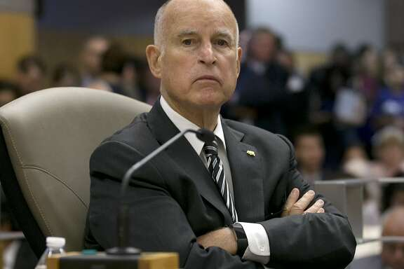 FILE -- In this July 13, 2017 file photo California Gov. Jerry Brown listens as members of the Senate Environmental Quality Committee discuss a pair of climate change bills he supports, in Sacramento, Calif. As his fourth and final term winds down Brown will spend the final 17 months in office working on California's housing crisis and fighting for ambitious projects to build a high-speed rail system and re-engineer California's water system. (AP Photo/Rich Pedroncelli, file)