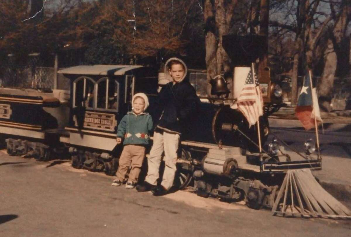 Brothers Mike and Doug Falcon pose in front of the Brackenridge Eagle train in a family photo. The boys, who were about 9 and 4 years old, were enjoying a ride aboard the miniature train with their father and grandmother on July 17, 1970, when two masked men brandishing a revolver jumped from the high brush and ordered the train's 75 passengers to hand over their valuables.