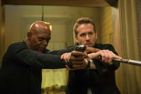 """This image released by Lionsgate shows Samuel L. Jackson, left, and Ryan Reynolds in """"The Hitman's Bodyguard."""" (Jack English/Lionsgate via AP) ORG XMIT: NYET862"""