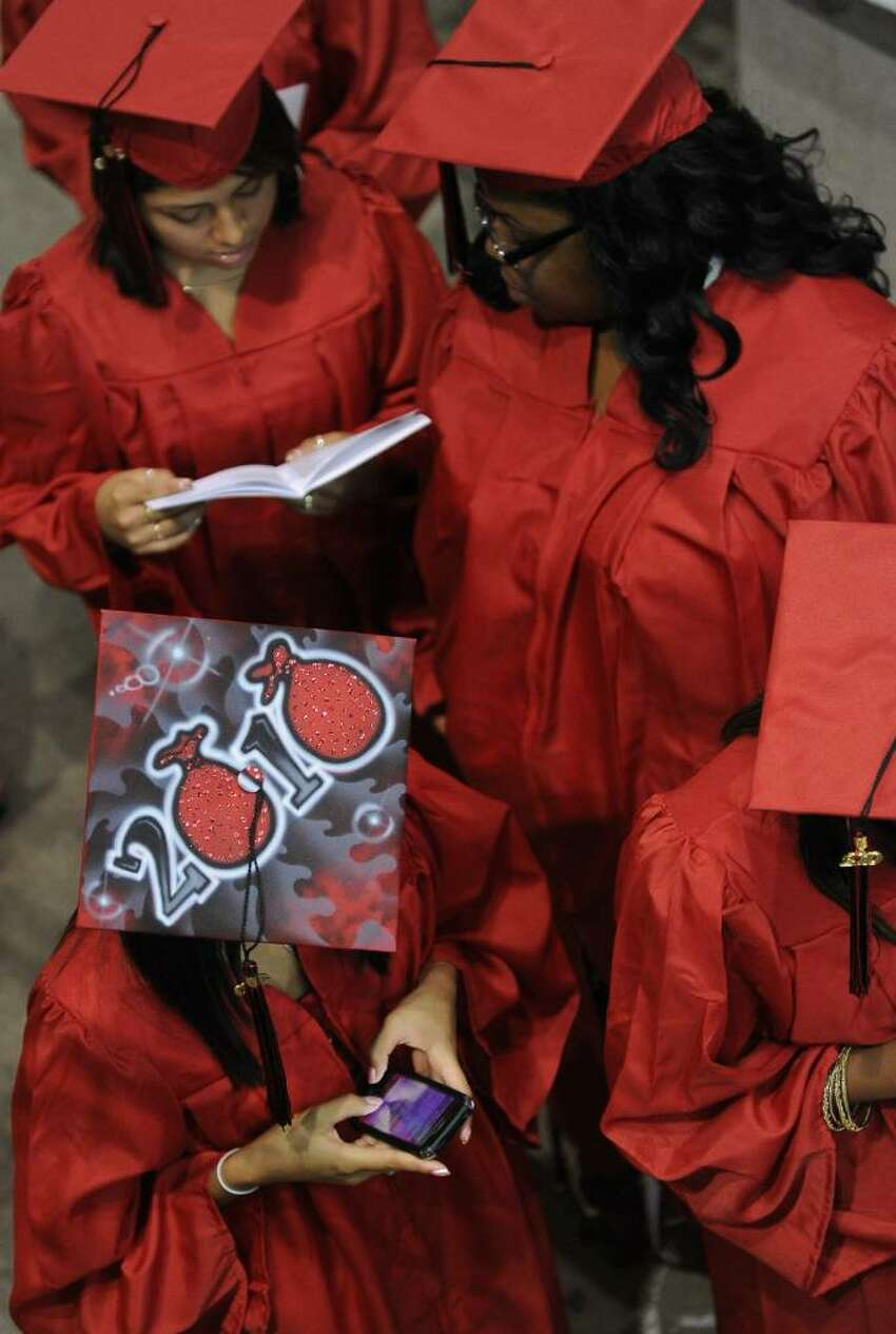 Graduate Jennifer Molina, bottom left, texts a message before heading in to be seated with her classmates, before the start of Central High School's Graduation Exercises at the Arena at Harbor Yard in downtown Bridgeport, Conn. on Thursday June 17, 2010.