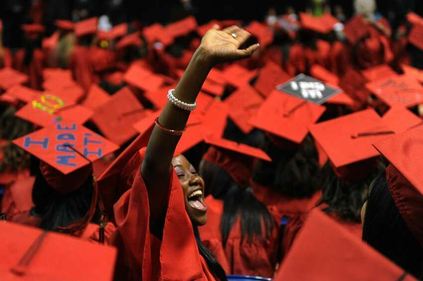 Graduate Mikeisha Smith waves to a family member in the sudience, during Central High School's Graduation Exercises at the Arena at Harbor Yard in downtown Bridgeport, Conn. on Thursday June 17, 2010.