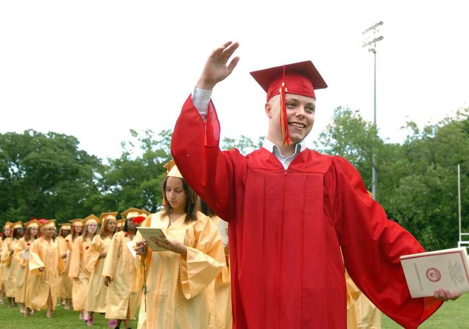 Marcin Niedzwiecki waves to friends and family in the audience as the class of 2010 marches onto Penders Field for the Stratford High School Graduation Ceremony Thursday June 17. Photo: Autumn Driscoll / Connecticut Post