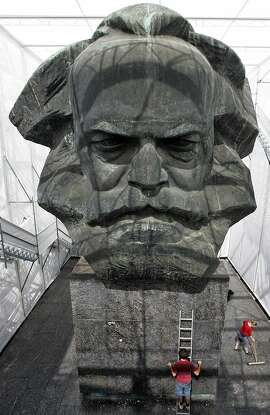"""Workers clean up at the so-called """"Temporary Museum of Modern Marx"""" walk on the steps past the plastic bust sculpture of German communist theorist Karl Marx in eastern German city of Chemnitz on June 17, 2008. The 13-meter sculpture by Soviet artist Lew Kerbel was unveiled in 1971 in the city then known as Karl-Marx-Stadt, has now been enclosed in a tent like covering by students of the art college in Linz, Austria. AFP PHOTO DDP / UWE MEINHOLD  GERMANY OUT (Photo credit should read UWE MEINHOLD/AFP/Getty Images)"""