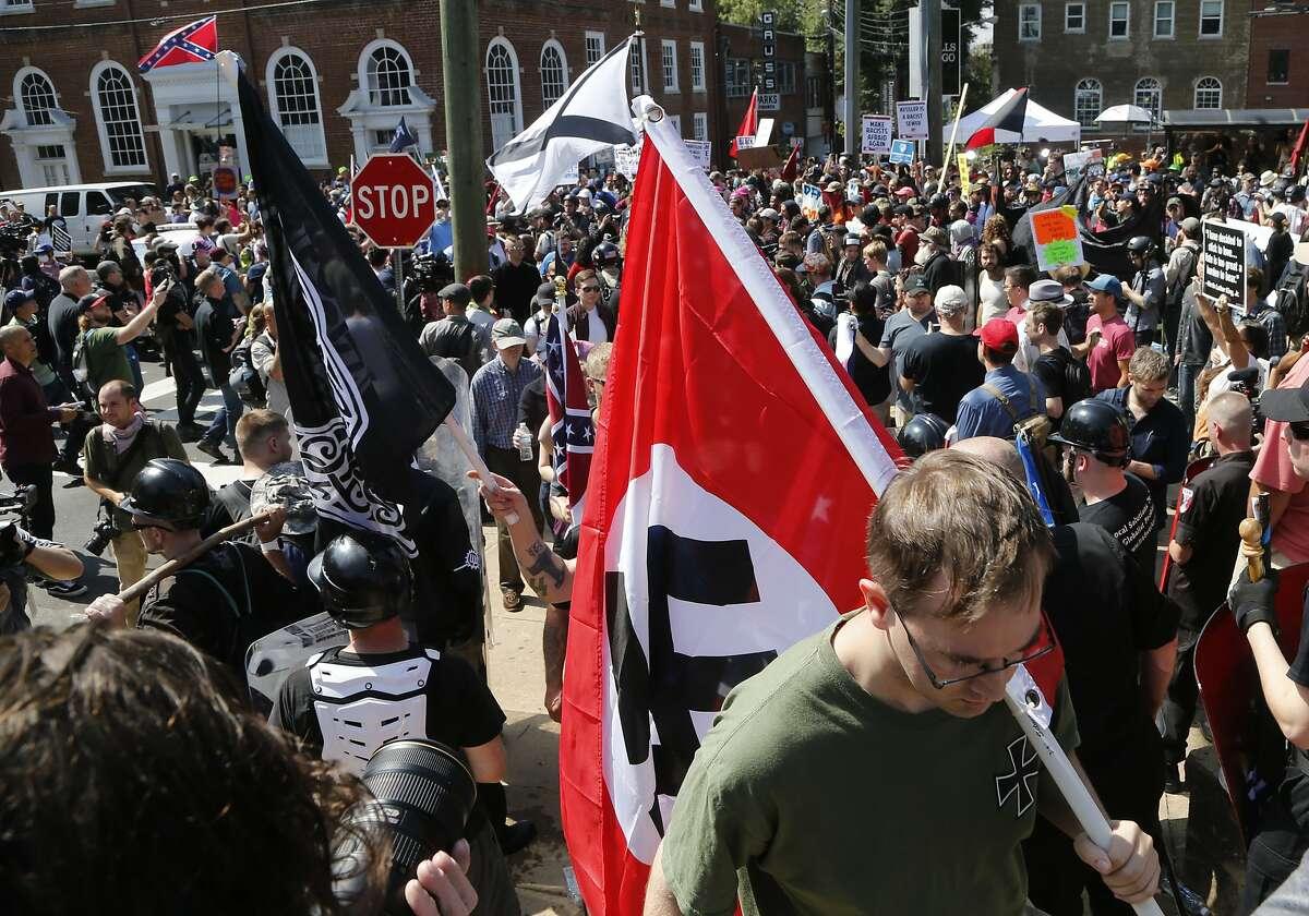 A white supremacist carries a Nazi flag Saturday in Charlottesville, Va.