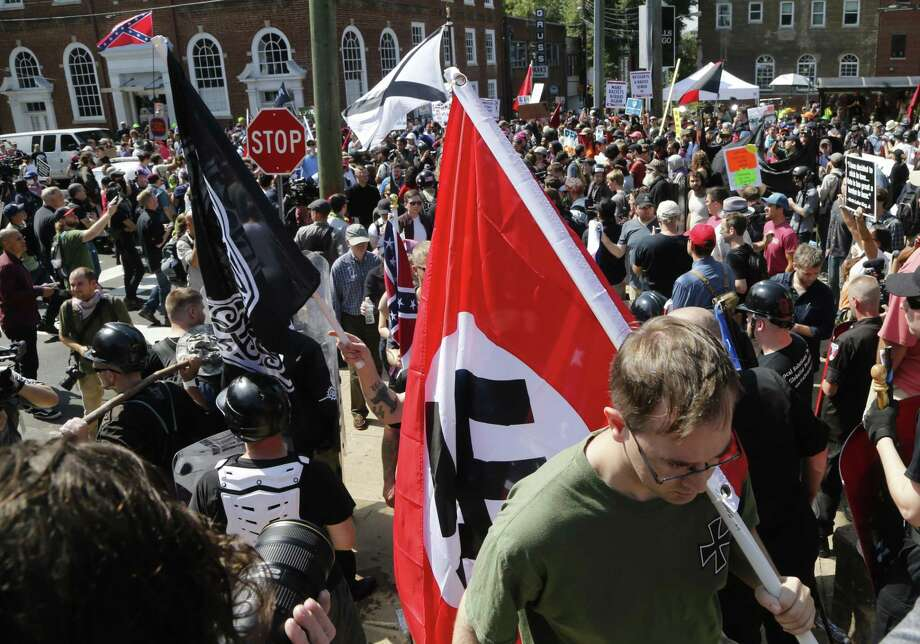 This Saturday, Aug. 12, 2017 image shows s white supremacist carrying a NAZI flag into the entrance to Emancipation Park in Charlottesville, Va. (AP Photo/Steve Helber) Photo: Steve Helber, STF / Associated Press / Copyright 2017 The Associated Press. All rights reserved.