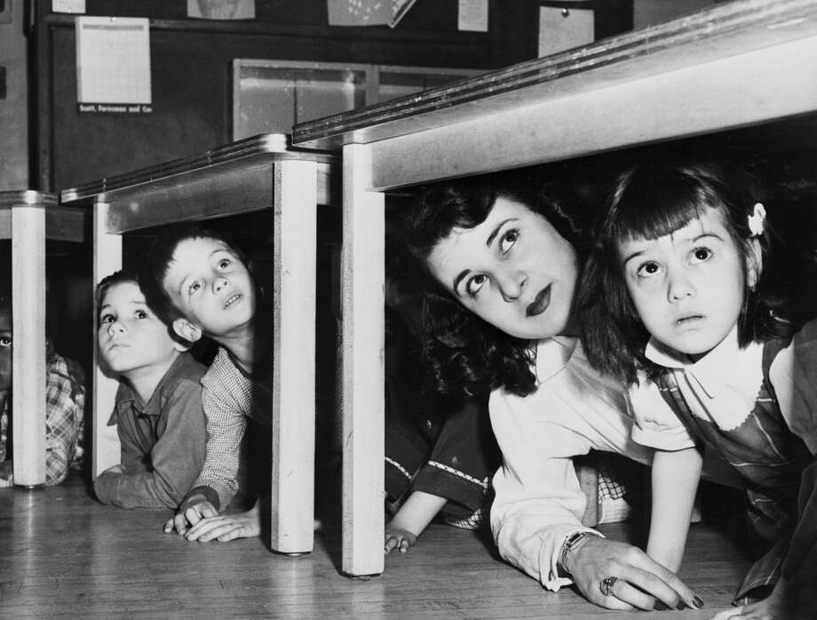 School children and a teacher peer from beneath the table where they took refuge at a Newark, New Jersey school in 1952 when the sirens howled the alert in the first state-wide air raid test. Photo: Bettmann/Bettmann Archive