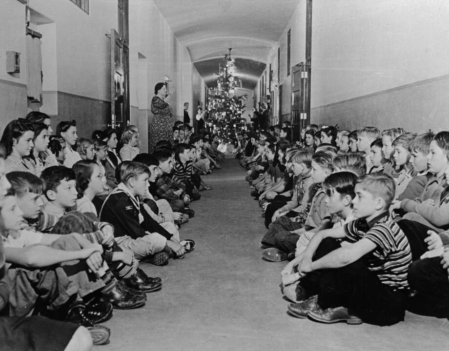 (Original Caption) In a Christmas atmosphere, children of Los Angeles' 74th Street School, under the guidance of teachers, stage an air raid precaution brill and sit quietly in one of the school's main halls. the boys and girls will be moved from classrooms in the event of a raid and will be grouped in such corridors.. Note the Christmas tree in the background. Photo: Bettmann/Bettmann Archive