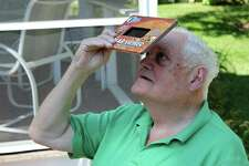 Martin Hamar of Wilton looks through a solar viewer to look directly at the sun.