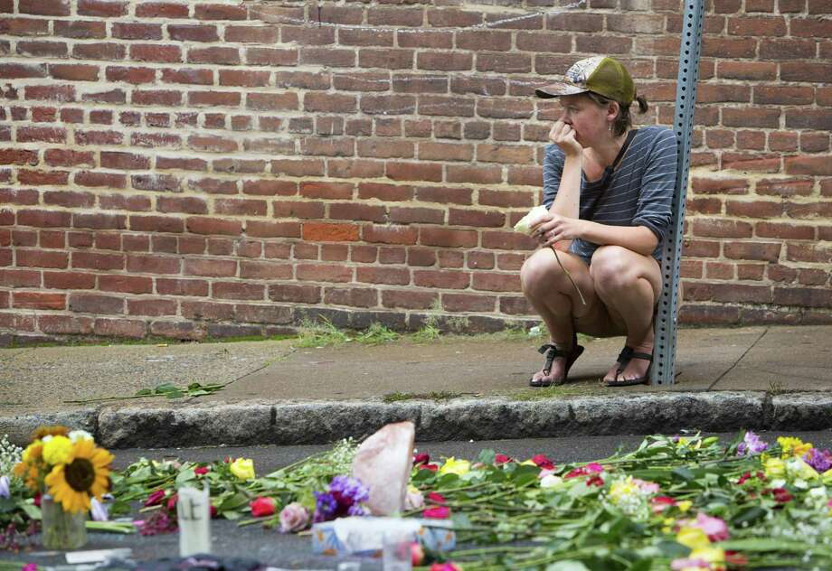 A woman leaves a flower at a memorial at 4th and Water Streets, Tuesday, Aug. 15 2017,  in Charlottesville, Va., where Heather Heyer was killed when a car rammed into a group of counterprotesters last weekend. Alex Fields Jr., is charged with second-degree murder and other counts after authorities say he rammed his car into a crowd of counterprotesters Saturday, where a white supremacist rally took place.  (AP Photo/Julia Rendleman) Photo: Julia Rendleman, FRE / Associated Press / Julia Rendleman