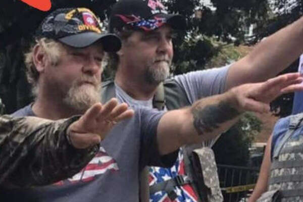 Source:  Twitter   Dozens of Twitter users shared photos of their veteran relatives who fought against the Nazis during WWII to protest against a Charlottesville man who pictured in a veteran's hat with the KKK salute, which is often mistaken for Hitler's salute.