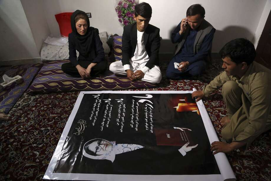 Maryam Hossaini (left) looks at a poster showing a picture of her sister, Najiba, who was killed in a suicide attack in Kabul last month. Photo: Rahmat Gul, Associated Press