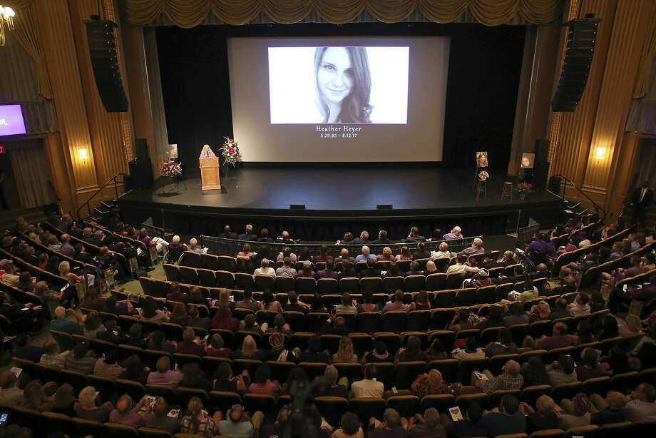 Heather Heyer's photo is projected over the stage where her mother, Susan Bro, speaks from a podium (left) at her funeral. Photo: Andrew Shurtleff, Associated Press