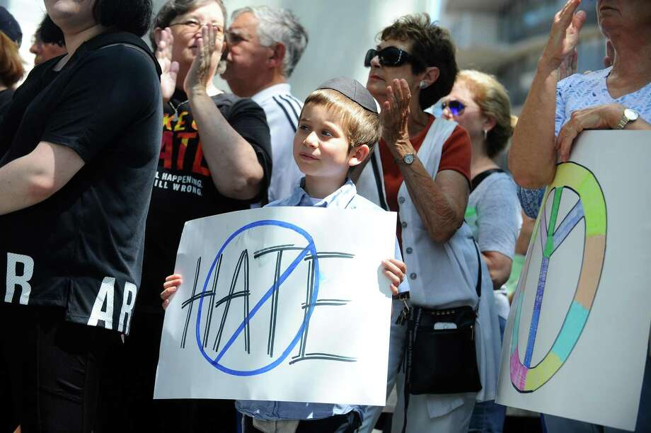 A young boy holds an anti-hate poster during the community vigil to stand against hatred and violence outside of Government Center in downtown Stamford on Wednesday. Photo: Michael Cummo / Hearst Connecticut Media / Stamford Advocate