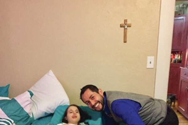Zack Johnson, owner of Klaussner Home Furnishings in Edwardsville, stands with 17-year-old Faren Wilson after he donated dual adjustable bases with memory foam/gel mattresses along with pillows, comforters and a teddy bear to her. Wilson suffers from Tisomy 18, which causes her to have refractory seizures and sever e developmental delays. She is on a pureed diet. She lives with her mother, Michelle Wilson, a sister and brother and her mother's boyfriend.